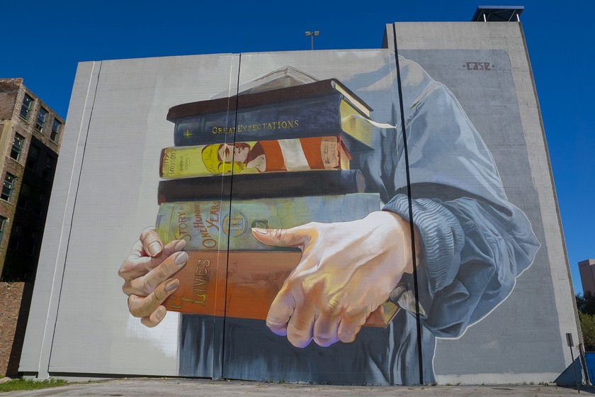 A stack of books mural by Case Maclaim in Jacksonville, Florida