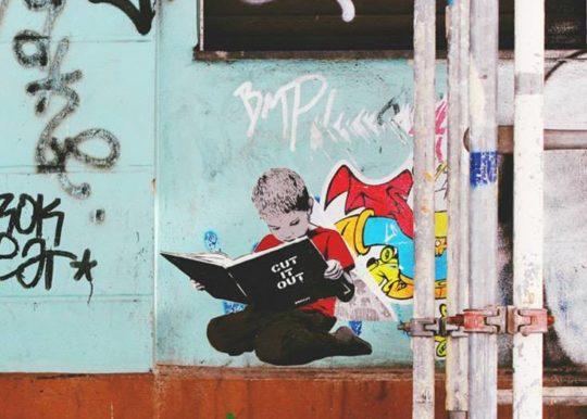 Boy reading a book - street art in Berlin