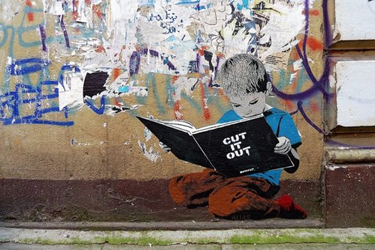 Boy reading a book - street art in Hamburg
