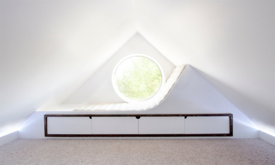 Minimalist attic window reading nook byStudio North