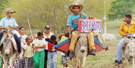 Biblioburro distributes books to patrons from the backs of two donkeys, Alfa and Beto