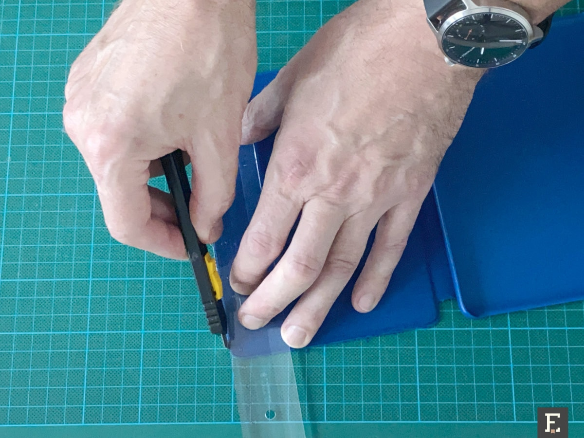 Use box cutter to remove fabric from the edges of the old Kindle case